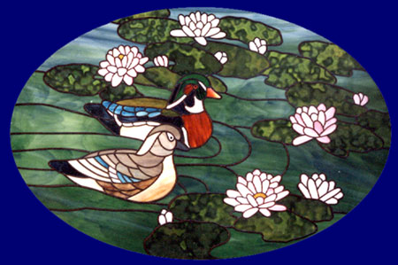 Pair of wood ducks on lily pond